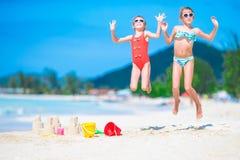 2 дет делая песок рокировать и имея потеху на тропическом пляже Стоковые Фото