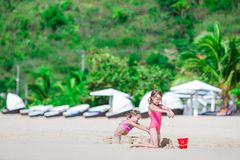 2 дет делая песок рокировать и имея потеху на тропическом пляже Стоковое Фото
