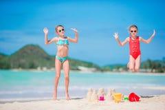 2 дет делая песок рокировать и имея потеху на тропическом пляже Стоковые Изображения