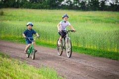 2 дет ехать на велосипедах на сельской дороге Стоковые Фото