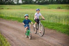 2 дет ехать на велосипедах на сельской дороге Стоковое фото RF