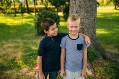 2 дет играют в парке 2 красивых мальчика в футболках и шорты имеют усмехаться потехи Они едят мороженое Стоковые Фотографии RF