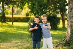 2 дет играют в парке 2 красивых мальчика в футболках и шорты имеют усмехаться потехи Они едят мороженое Стоковые Изображения