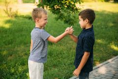 2 дет играют в парке 2 красивых мальчика в футболках и шорты имеют усмехаться потехи Они едят мороженое Стоковое Фото