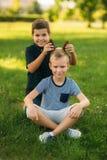 2 дет играют в парке 2 красивых мальчика в футболках и шорты имеют усмехаться потехи Они едят мороженое Стоковая Фотография
