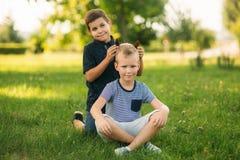 2 дет играют в парке 2 красивых мальчика в футболках и шорты имеют усмехаться потехи Они едят мороженое Стоковое Изображение RF