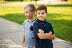 2 дет играют в парке 2 красивых мальчика в футболках и шорты имеют усмехаться потехи Они едят мороженое Стоковое Изображение