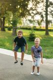 2 дет играют в парке 2 красивых мальчика в футболках и шорты имеют усмехаться потехи Они едят мороженое Стоковая Фотография RF