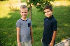 2 дет играют в парке 2 красивых мальчика в футболках и шорты имеют усмехаться потехи Они едят мороженое Стоковое фото RF