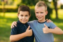 2 дет играют в парке 2 красивых мальчика в футболках и шорты имеют усмехаться потехи Они едят мороженое Стоковые Фото