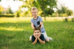 2 дет играют в парке 2 красивых мальчика в футболках и шорты имеют усмехаться потехи Они едят мороженое Стоковые Изображения RF