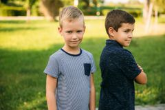 2 дет играют в парке 2 красивых мальчика в футболках и шорты имеют усмехаться потехи Стоковые Фотографии RF