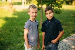 2 дет играют в парке 2 красивых мальчика в футболках и шорты имеют усмехаться потехи Стоковое Изображение