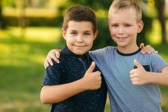 2 дет играют в парке 2 красивых мальчика в футболках и шорты имеют усмехаться потехи Стоковые Фото