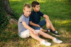 2 дет играют в парке 2 красивых мальчика в футболках и шорты имеют усмехаться потехи Стоковое Фото