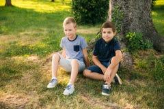 2 дет играют в парке 2 красивых мальчика в футболках и шорты имеют усмехаться потехи Стоковая Фотография RF