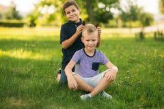 2 дет играют в парке 2 красивых мальчика в футболках и шорты имеют усмехаться потехи Стоковая Фотография