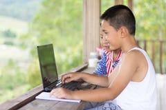 2 дет исследуют интернет и старую компьтер-книжку edu стоковые фотографии rf