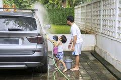 2 дет и их отец моют автомобиль дома стоковые фотографии rf