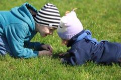 2 дет лежа на голове gass головной касающей и имея потеху смотря один другого Стоковая Фотография