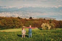 2 дет, маленький брат и старшая сестра, играя совместно outdoors в швейцарских полях с взглядом на женевском озере Стоковое Фото