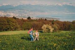 2 дет, маленький брат и старшая сестра, играя совместно outdoors в швейцарских полях с взглядом на женевском озере Стоковые Изображения