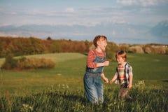 2 дет, маленький брат и старшая сестра, играя совместно outdoors в швейцарских полях с взглядом на женевском озере Стоковое Изображение RF