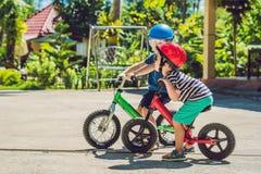 2 дет мальчиков имея потеху на велосипеде баланса на дороге страны тропической Стоковое Фото