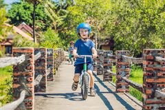 2 дет мальчиков имея потеху на велосипеде баланса на bridg Стоковое Изображение