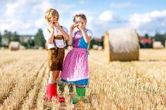 2 дет, мальчик и девушка в традиционных баварских костюмах в пшеничном поле Стоковое Фото