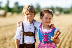 2 дет, мальчик и девушка в традиционных баварских костюмах в пшеничном поле Стоковая Фотография