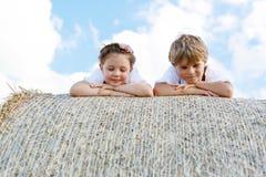 2 дет, мальчик и девушка в традиционных баварских костюмах в пшеничном поле с связками сена Стоковая Фотография RF