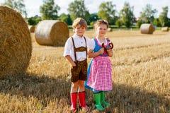2 дет, мальчик и девушка в традиционных баварских костюмах в пшеничном поле Стоковое Изображение RF