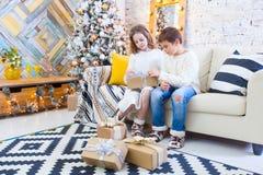 2 дет мальчик и девушка на рождественской елке на софе с подарками В светлых цветах Стоковая Фотография