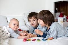 3 дет, младенец и его более старые братья в кровати в mornin Стоковое Изображение