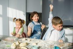 3 дет подготавливают что-то от теста Стоковое Фото