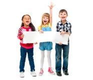 3 дет при открытые рти держа пустой лист бумаги стоковое фото rf