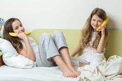2 дет сестры в пижамах, бананах как телефоны Стоковое Изображение RF