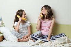 2 дет сестры в пижамах играют в утре в кровати Держите бананы как телефоны говоря и смеясь над Стоковая Фотография RF