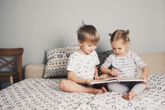 2 дет сидя на кровати и читая книгу Стоковое фото RF