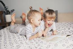 2 дет сидя на кровати и читая книгу Стоковое Изображение RF