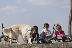 3 дет сидя на поле принимая внешнюю закуску Стоковая Фотография