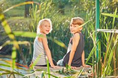 2 дет сидя на пристани озера Стоковое Фото