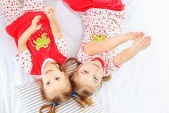 2 дет смеясь над и лежа в пижамах Концепция ребенка Стоковые Фото