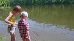 2 дет улавливают рыб с рыболовными удочками на речном береге Красивейший ландшафт лета воссоздание обеда напольное сток-видео