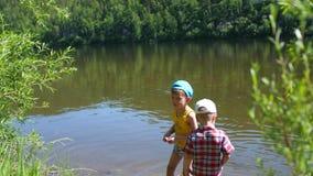 2 дет улавливают рыб с рыболовными удочками на речном береге Красивейший ландшафт лета воссоздание обеда напольное акции видеоматериалы