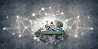 2 дет школьного возраста с книгой исследуя этот большой мир Стоковые Изображения RF