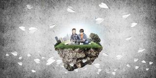 2 дет школьного возраста с книгой исследуя этот большой мир Стоковое Фото