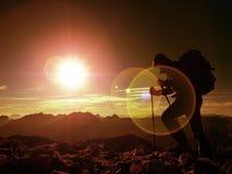 Дефект пирофакела объектива Hiker человека с прогулкой рюкзака на скалистом пике Человек идя o Стоковые Фото
