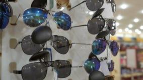 Дешевые солнечные очки, низкое качество показанное в магазине, использованы для защиты глаз от солнца видеоматериал